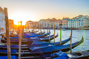 Foto op Aluminium Gondolas Gondolas moored docked on pier of Grand Canal water in Venice city. Baroque style colorful buildings along Grand Canal. View against sun. Amazing Venice cityscape at sunset. Veneto Region, Italy