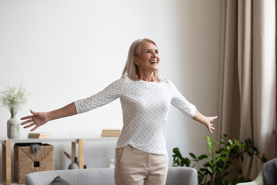 Overjoyed mature grandmother standing with outstretched arms near comfortable couch, breathing fresh air, enjoying freedom, happy life moment. Smiling older woman feeling thankful for good day.