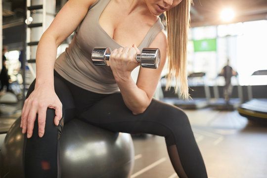 Mid section portrait of beautiful young woman holding dumbbell during strength workout in sunlit gym, copy space