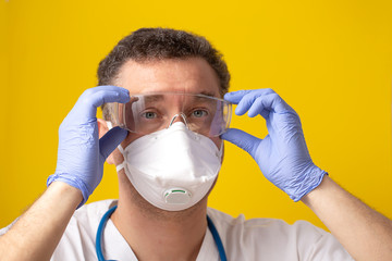 Medical worker wearing glasses as personal protective equipment on yellow background