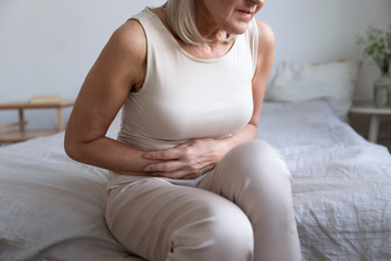Cropped image older unhealthy woman embracing belly, suffering from strong stomach ache. Unhappy middle aged lady feeling discomfort in abdomen, pancreatitis gastritis diarrhea problem concept.