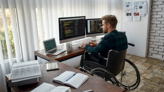 Full concentration. Back view of young professional web developer in a wheelchair writing program code on multiple computer screens while sitting at his workplace in the modern office
