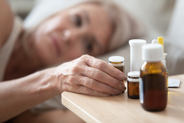 Close up focus on wrinkled female hand taking glass bottle with pills. Head shot unhealthy middle...