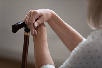 Older retired woman holding hands on wooden cane, close up. Tired mature female pensioner resting...