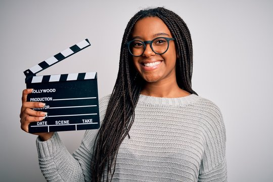 Young african american director girl filming a movie using clapboard over isolated background with a happy face standing and smiling with a confident smile showing teeth