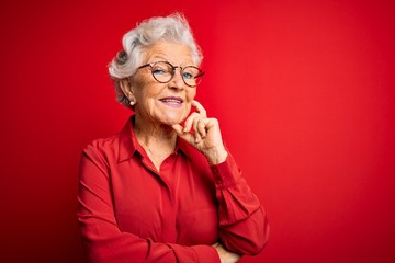 Senior beautiful grey-haired woman wearing casual shirt and glasses over red background looking confident at the camera with smile with crossed arms and hand raised on chin. Thinking positive. Wall mural