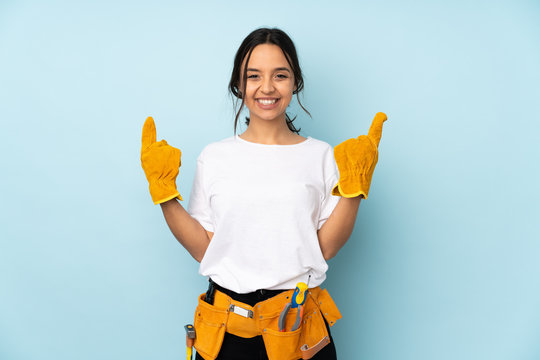 Young electrician woman isolated on blue background pointing up a great idea