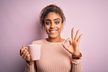 Young african american afro girl drinking cup of coffee over isolated pink background doing ok sign with fingers, excellent symbol