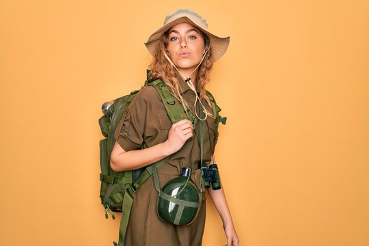 Young blonde explorer woman with blue eyes hiking wearing backpack and water canteen looking at the camera blowing a kiss on air being lovely and sexy. Love expression.