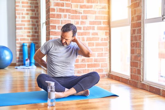Middle age handsome sportman sitting on mat doing stretching yoga exercise at gym Suffering of neck ache injury, touching neck with hand, muscular pain