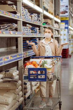 woman with medical facemask in supermarket outraged about lack of products on shelves.