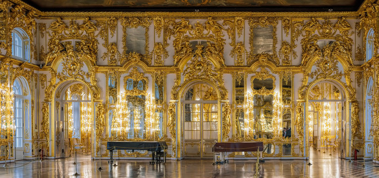 Magnificent carved baroque decor, candlesticks, mirrors, sculptural and ornamental gilded carvings covering the walls of the Catherine Palace of Tsarskoe Selo. Saint-Petersburg, Russia.