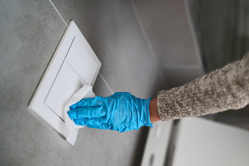 Surface sanitizing wipes of bathroom surfaces, toilet flush wall button wiping paper towel sanitizer with gloves.