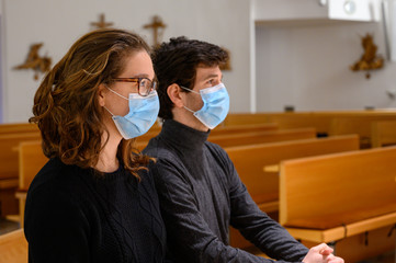 A young couple in face masks praying in a church during the COVID-19 pandemic. Bratislava, Slovakia.