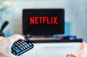 A young man watches Netflix on his TV and at home. TV remote in the foreground, blurred background on the TV.