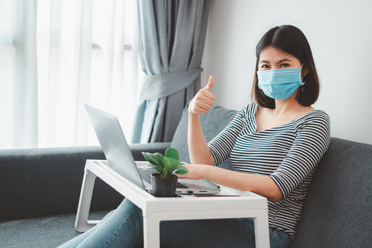 Asian woman wearing face mask working at home