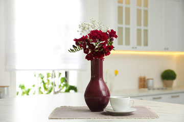 Beautiful bouquet with freesia flowers and cup on table in kitchen