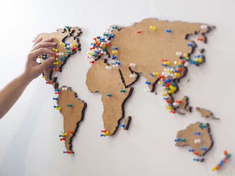 Woman hand putting red pin and marking location at wooden world map