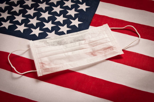 CORONAVIRUS. Protective medical mask on the background of the American flag . Concept of protection against coronavirus.