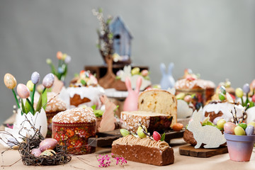 Easter cake orthodox sweet bread kulich and colorful chocolate eggs on festive table
