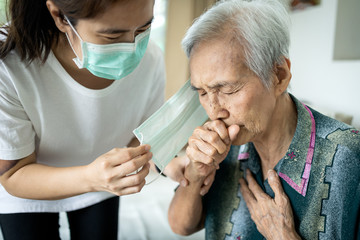 Old people have illness,fever,cough and difficulty breathing,infectious symptoms of flu,pandemic of Covid-19,asian caregiver wearing a mask to sick senior woman,prevent outbreak,spread of Coronavirus