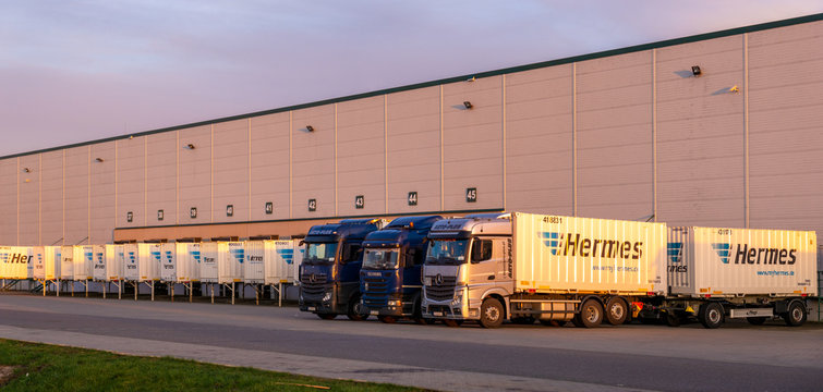 Scania and Mercedes trucks carrying containers with the Hermes and DHL logo in the DB Schenker logistics center-Goleniow,Poland-March 2020.