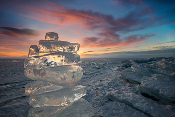 Sunset reflected in a large block of ice hummock on the frozen lake background.