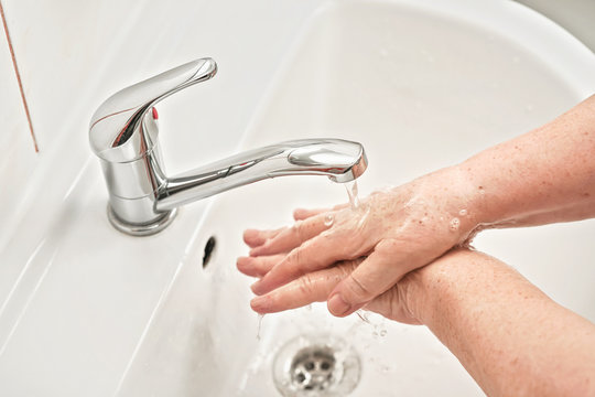 Elderly woman washing her hands with soap under tap water faucet, closeup detail. Can be used as hygiene illustration concept during ncov coronavirus / covid 19 outbreak prevention