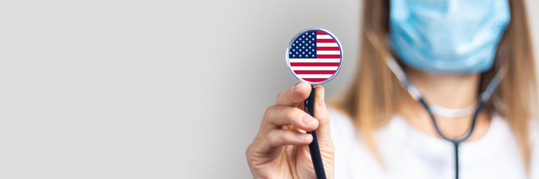 female doctor in a medical mask holds a stethoscope on a light background. Added flag of United States of America. Concept medicine, level of medicine, virus, epidemic. Baner