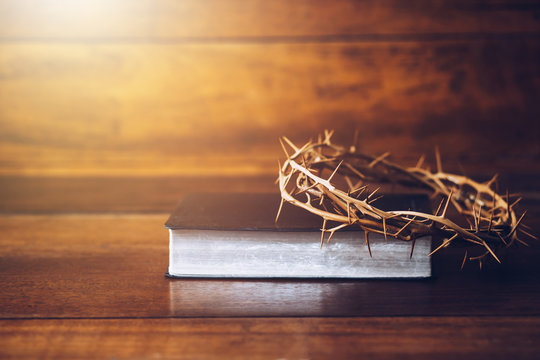 Close up of crown of thorns of Jesus on top of the holy bible on wooden table can be used for Christian concept , Easter concept