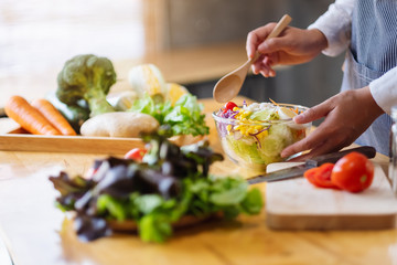 Closeup image of a female chef cooking and holding a bowl of fresh mixed vegetables salad in kitchen