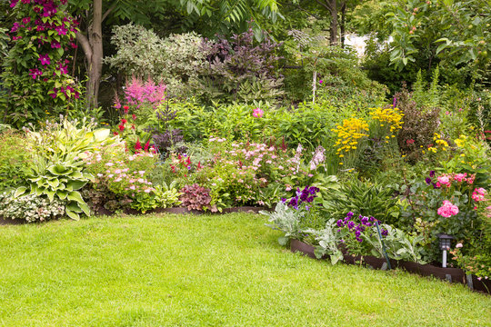Beautiful colorful flower garden with blooming flower beds and a green lawn in summer