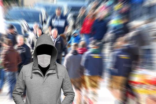 Mann mit Mundschutz steht in der Menschenmenge
