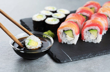Printed roller blinds Sushi bar Sushi maki with avocado, sushi philadelphia, soy sauce and wasabi. Chopsticks taking portion of sushi roll.