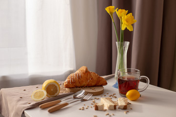 Photo on textile frame Narcissus In the room on the table serving breakfast with a cup of tea, croissants, lemons and yellow narcis in a glass vase