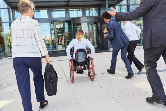 Business people running next to businesswoman in a wheelchair