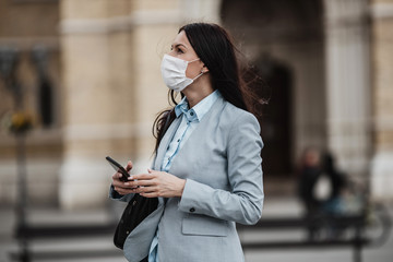 Young and elegant business woman standing on empty city street and wearing protective mask to protect herself from dangerous flu or virus. Corona virus or Covid-19 concept.