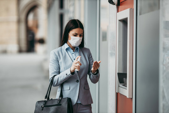 Elegant woman with protective mask standing on city street and using alcohol spray to disinfect her hands after use of ATM machine. Corona or Covid-19 virus pandemic prevention and healthcare concept.