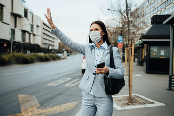 Elegant business woman with protective mask standing alone on empty street and calling for bus or taxi transport with raised hand. Corona virus or Covid-19 lifestyle concept.