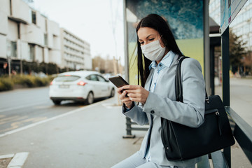 Elegant business woman with protective mask sitting alone on empty street and waiting for bus or taxi transport while using phone. Corona virus or Covid-19 lifestyle concept. Fotobehang