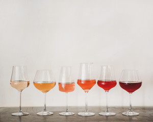 Various shades of Rose wine in stemmed glasses placed in line from light to dark colour on concrete table, white wall background behind, copy space. Wine bar, wine shop, wine tasting concept