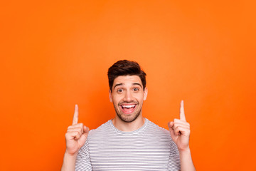 Closeup photo of attractive funny guy hold hands fingers direct up empty space excited good mood sales person nice offer wear striped t-shirt isolated bright orange color background - fototapety na wymiar