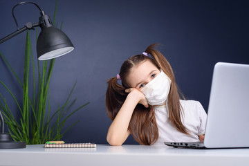 Distance learning online education. schoolgirl in medical mask studying at home, working at laptop...
