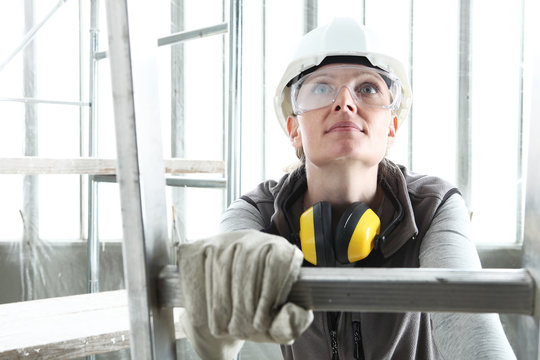 smiling woman construction worker builder on ladder wearing white helmet and hearing protection headphones on interior site building background