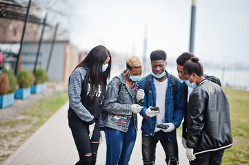 Group of african teenagers friends at park wearing medical masks protect from infections and diseases coronavirus virus quarantine, read shocked news on phone.