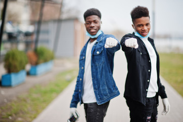 Two african teenagers friends at park wearing medical masks protect from infections and diseases coronavirus virus quarantine.