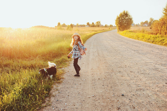 happy child girl walking country road with her dog. Enjoying summer vacations, rural living concept