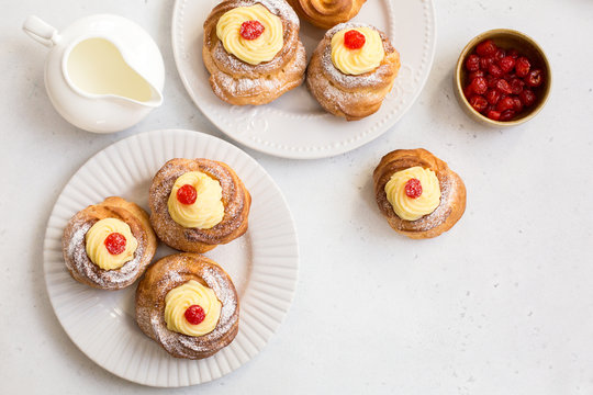 Italian pastry - zeppole di San Giuseppe - baked cream puffs made from choux pastry, filled and decorated with custard cream and cherry. It is eaten to celebrate Saint Joseph's Day.