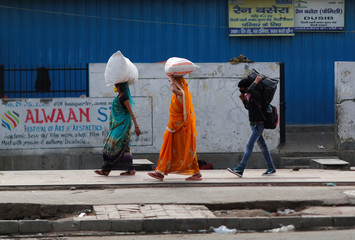 People carrying their luggage walk towards a bus station to return to their cities and villages during lockdown by the authorities to limit the spreading of coronavirus disease (COVID-19), in New Delhi