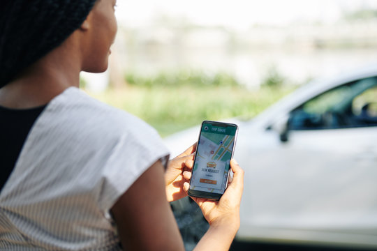 Female driver accepting new request in car sharing application, selective focus